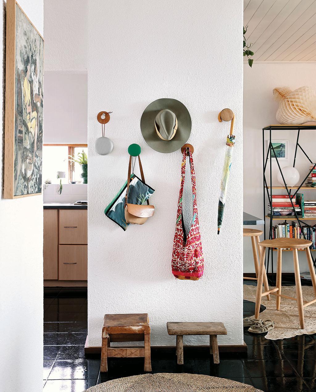 vtwonen special zomerhuizen 07-2021 | wandhaken met een hoed, verschillende tassen en twee houten trapjes