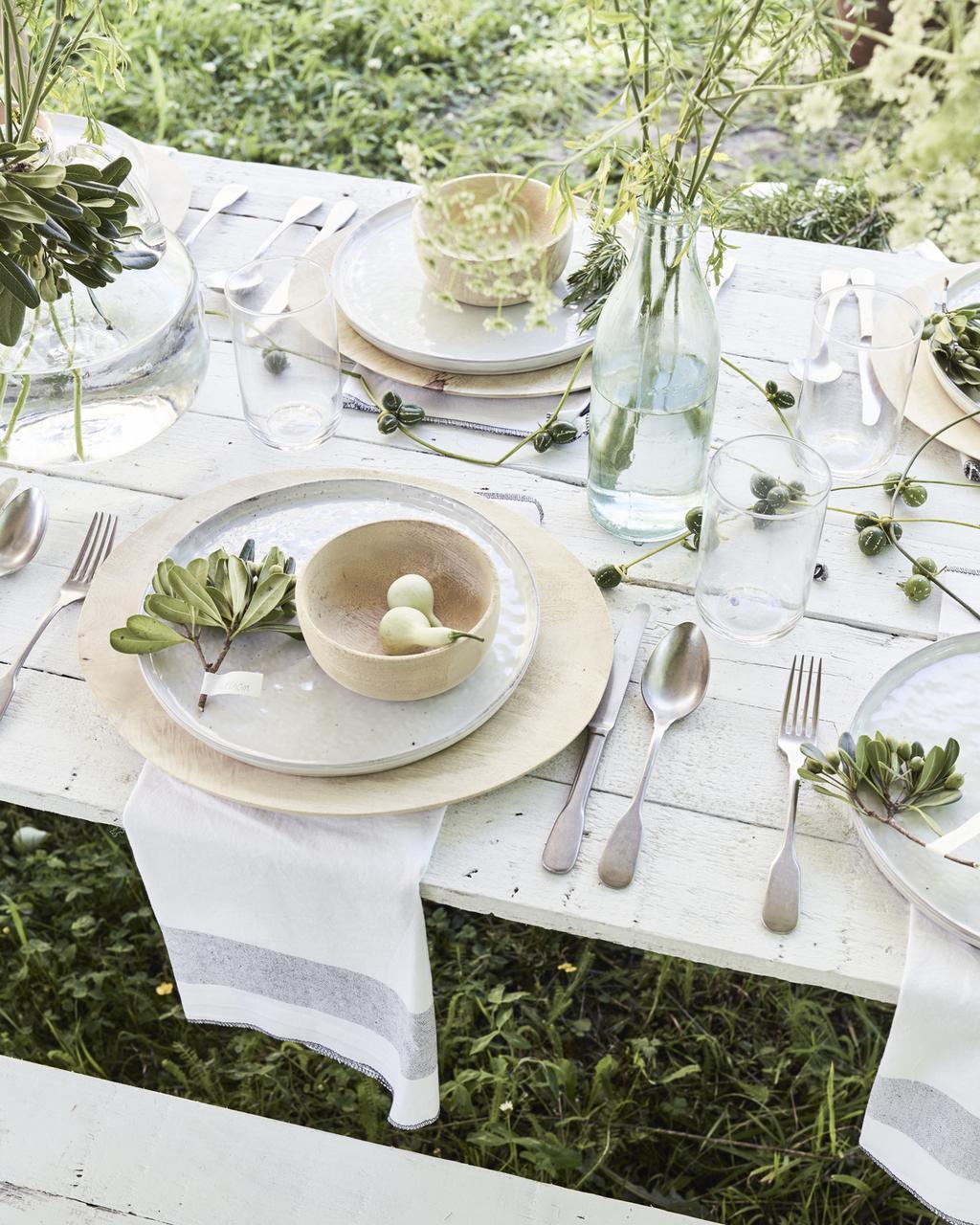Een vrolijk gedekte tuintafel met veel groen en wit.