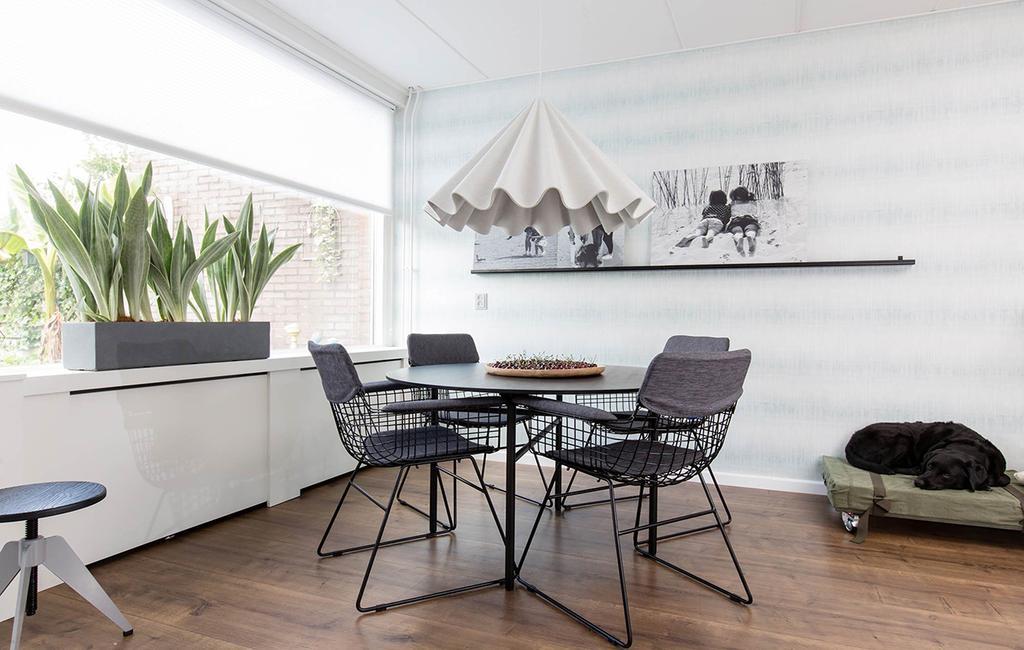 Vergrijsd blauw interieur eetkamer met vilten hanglamp en een ronde tafel