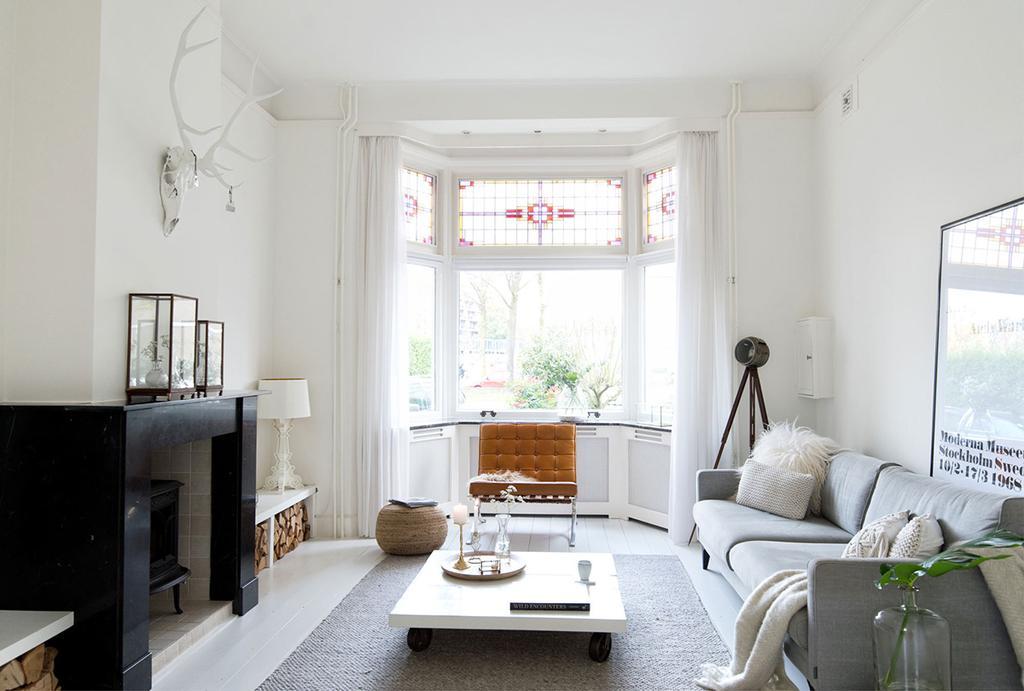 Lichte woonkamer met glas-in-loodramen in erker