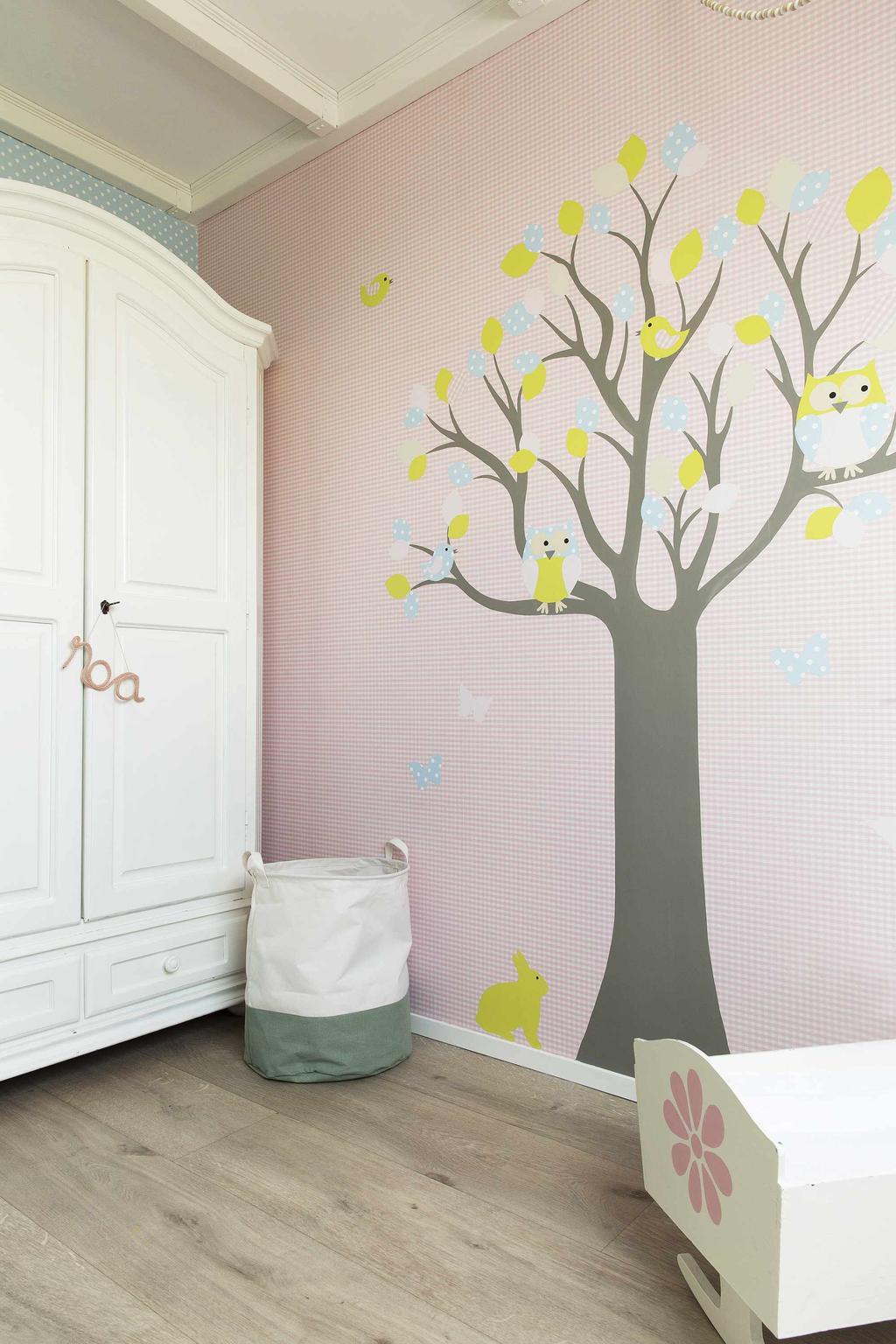 Meisjeskamer met roze muur met boom