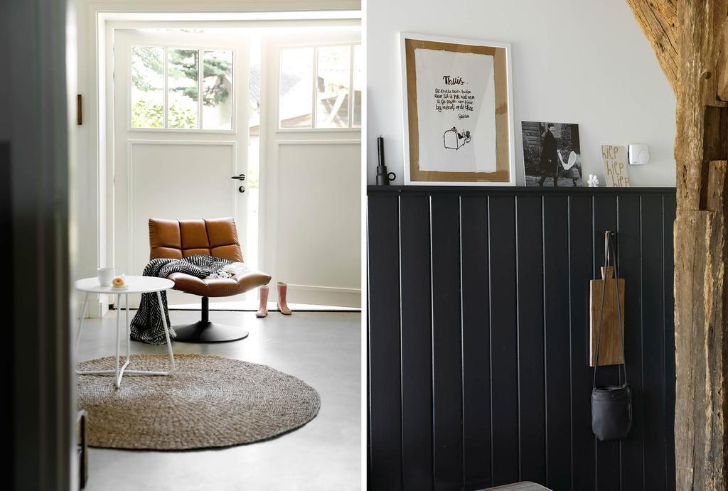 Leren fauteuil in zithoek zwarte lambrisering met fotolijsten