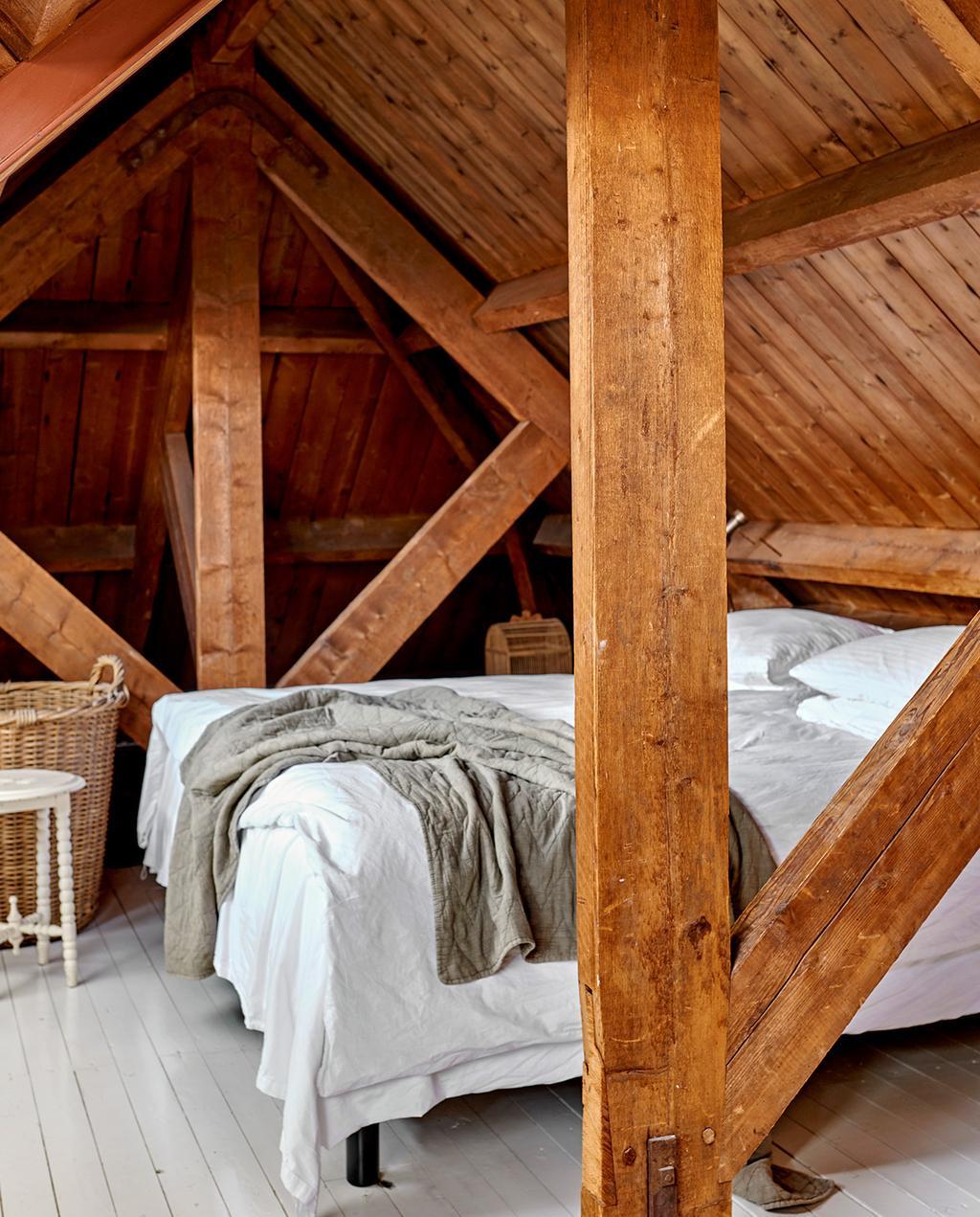 vtwonen 07-2021 | zolder slaapkamer met een schuin dak en een wit opgemaakt bede
