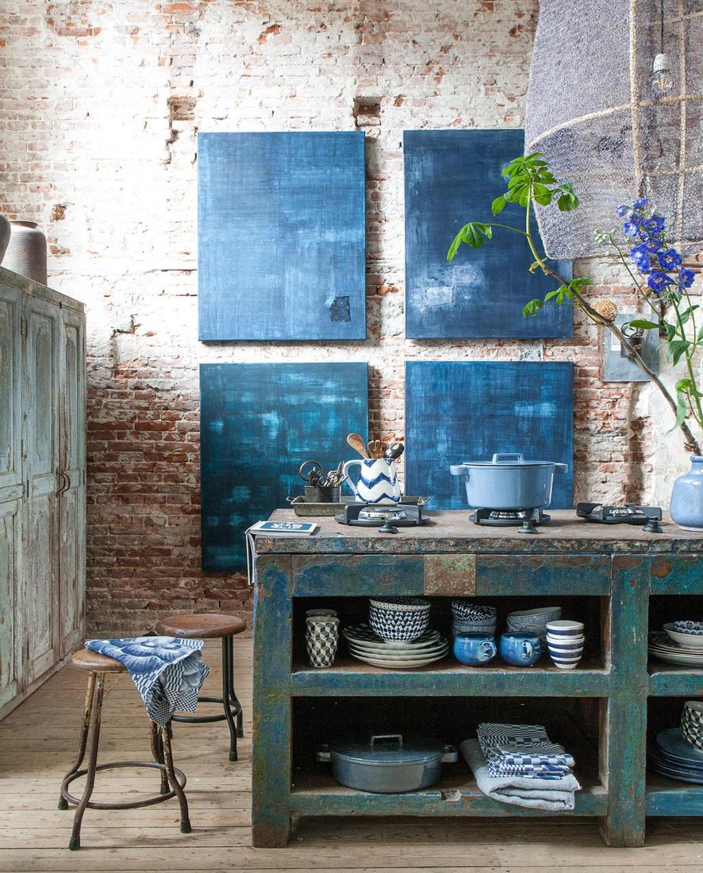 vtwonen 10-2016 | industriële keuken met op achtergrond 4 samenhangende blauwe schilderijen