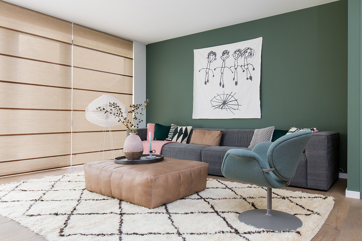 Woonkamer met groene muur en vouwgordijnen