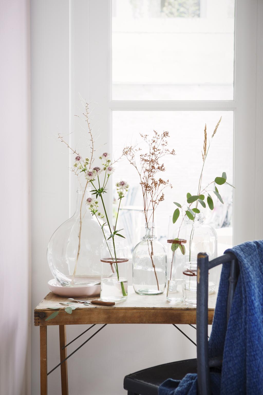 bureau met glazen vazen met bloemen in het raamkozijn