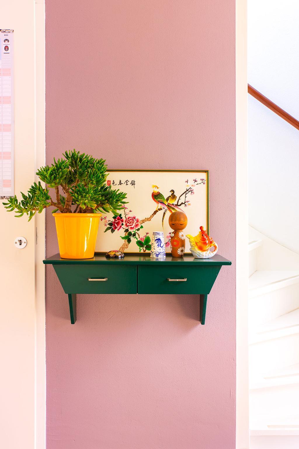 Plank met chinoiserie en kokeshi tegen een roze wand