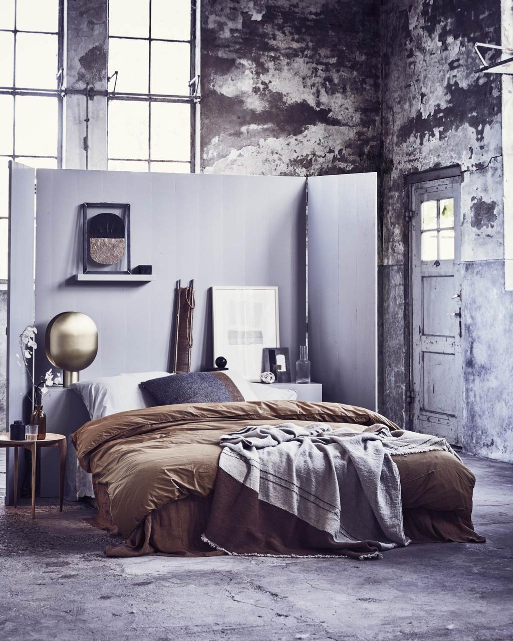 Kunst aan de muur boven het bed in de slaapkame rmet donkere, blauwe en roestbruine kleuren.