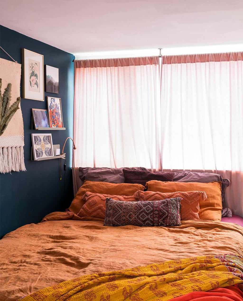 vtwonen 07-2021 | een bed met oranje dekbedovertrek in de slaapkamer van Esther