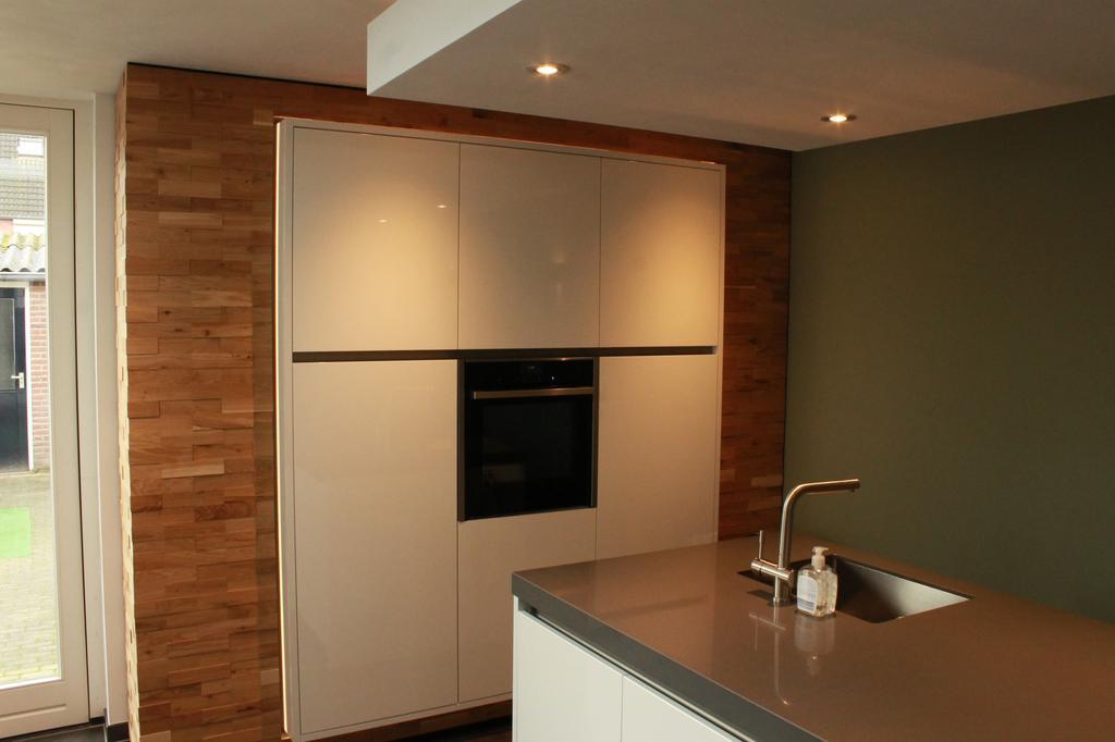 apparatenwand-rondom-bekleedt-met-eiken-houten-strips-in-de-apparatenwand-zit-een-neff-full-steam-oven-b47fs26n0-en-een-neff-koelkast-ki2423d30