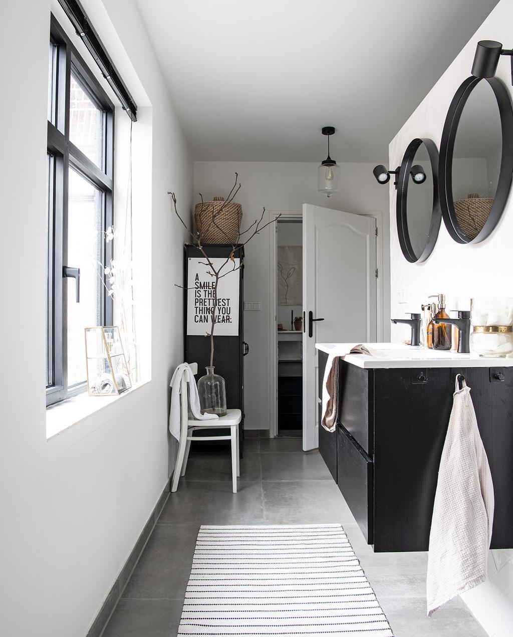 vtwonen 04-2021 | badkamer met zwart wastafelmeubel, ronde spiegels en witte stoel