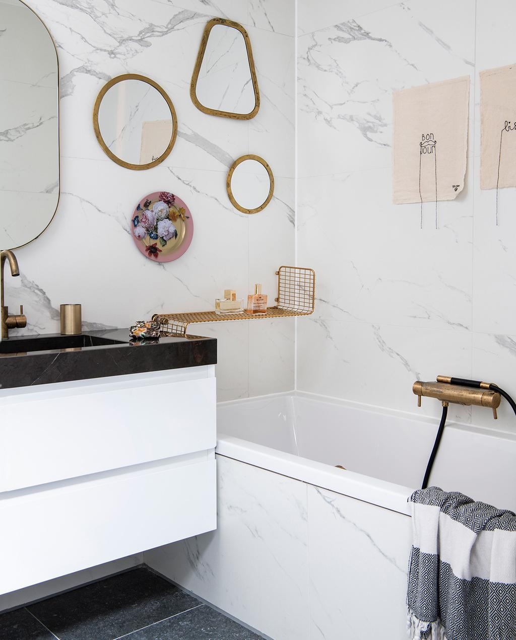 vtwonen 06-2021 | badkamer met marmeren muur en bad, en drie gouden spiegels aan de wand