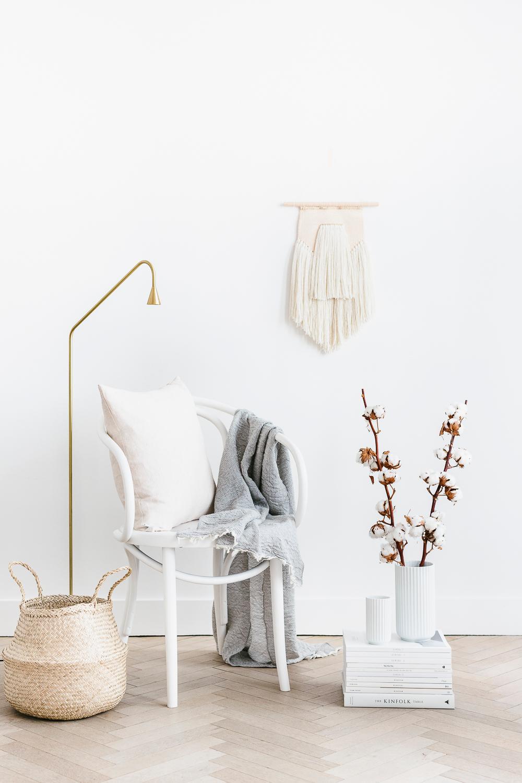 voorjaarshuis beige met stoel en staande lamp en takken en een mand
