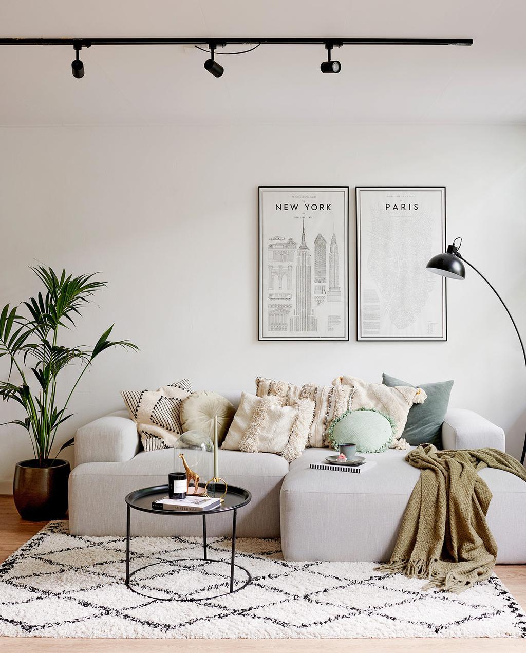 vtwonen special tiny houses | grijze grote bank in de woonkamer van het appartement van Maud en Maarten, met een New York en Amsterdam poster aan de muur