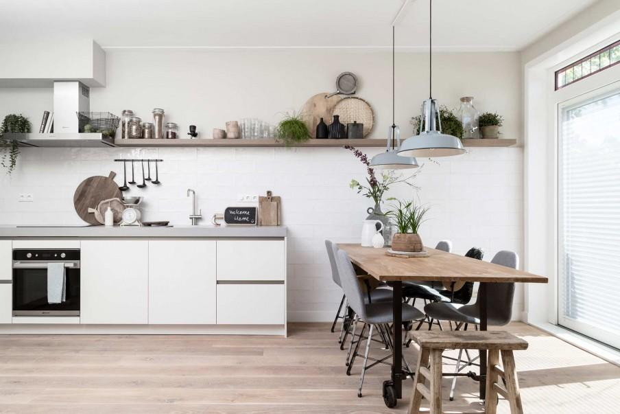 Witte keuken met houten wandplank en eethoek