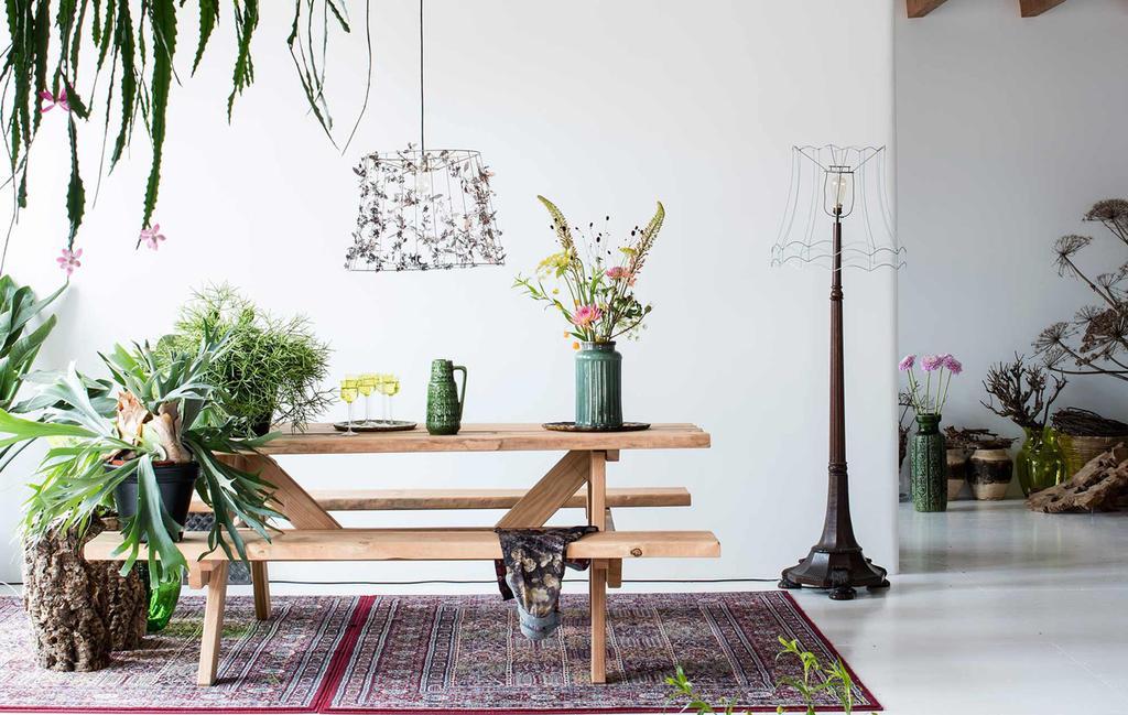 houten eettafel in bohemian interieur met veel kamerplanten en Perzisch tapijt