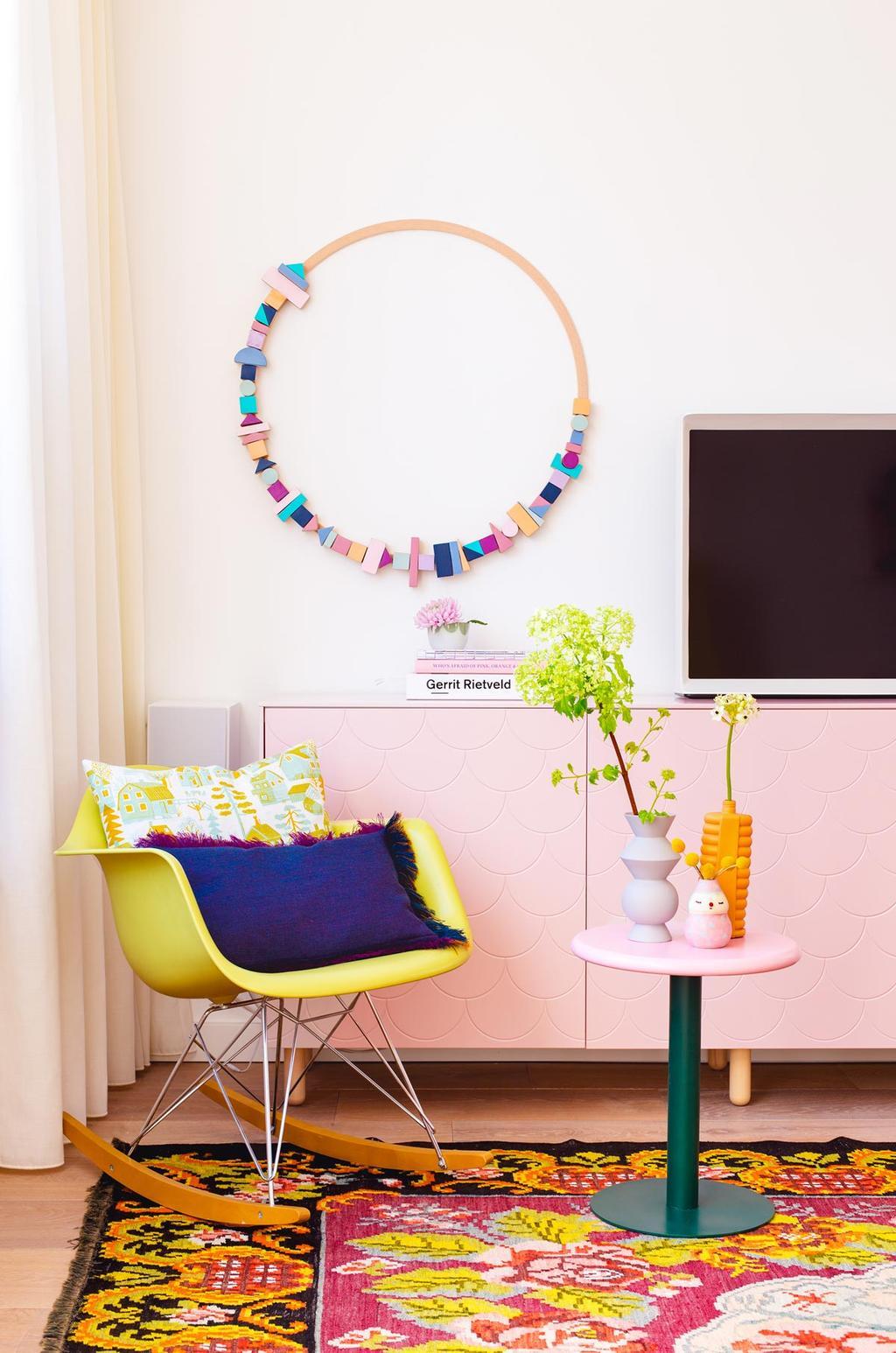 Blokjeskrans op de muur met roze dressoir en gele stoel