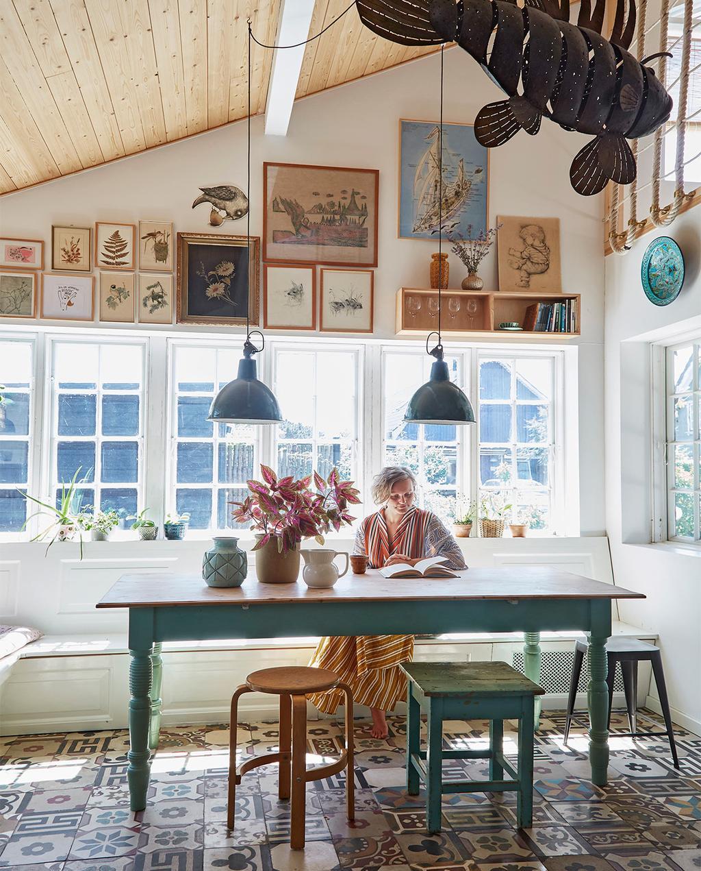 vtwonen special zomerhuizen 07-2021 | een blauw groene tafel, Josephine zit op een stoel, met allemaal verschillende school posters op de achtergrond
