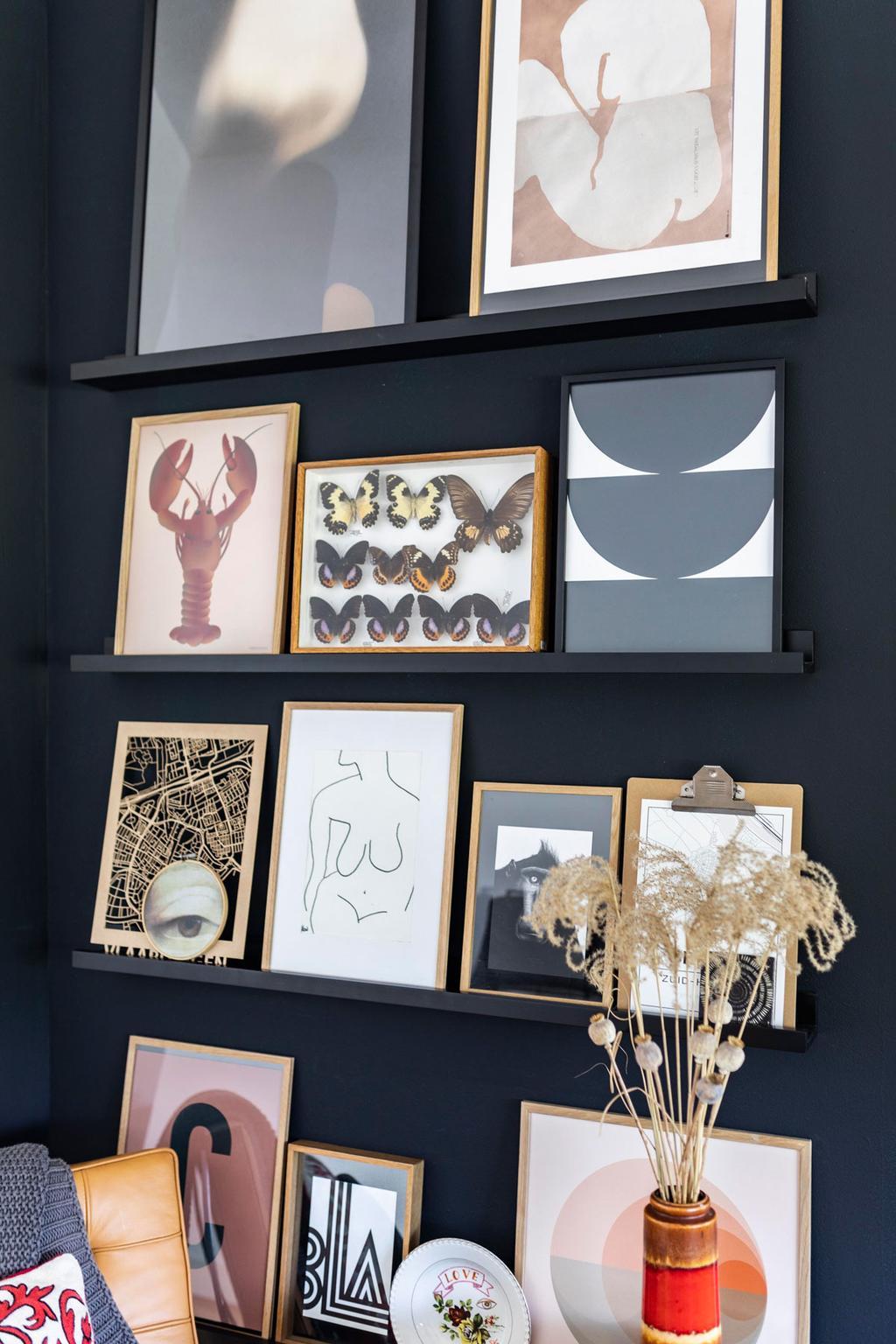 Zwarte muur met verschillende lijsten op plankjes