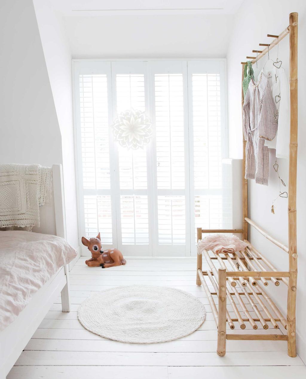 slaapkamer met wit rond vloerkleed en houten kledingrek