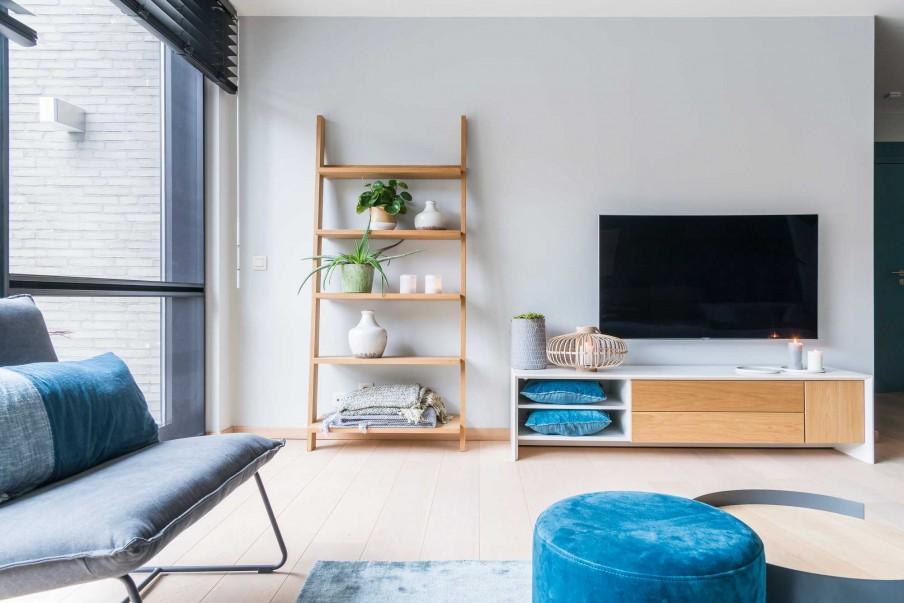 Woonkamer met stoel en tv op kast in blauwe kleuren