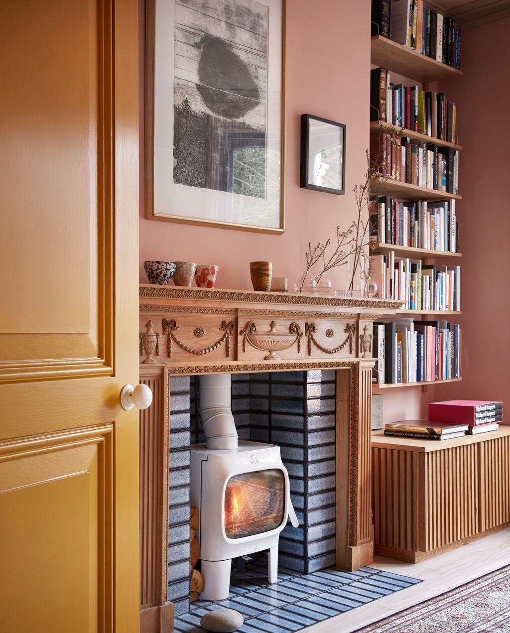 vtwonen 05-2020 | styling colourboost zitkamer met roze muren, antiek houten schouw en hoge boekenplankwand