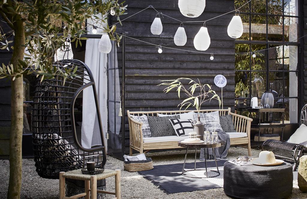 Een tuin waarin veel zwart voorkomt, bijvoorbeeld in de vorm van de schutting.
