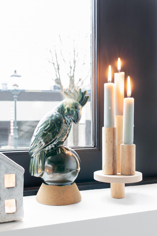 DIY houten kaarsenstandaard met blauwe kaarsen en een kaketoe in de vensterbank