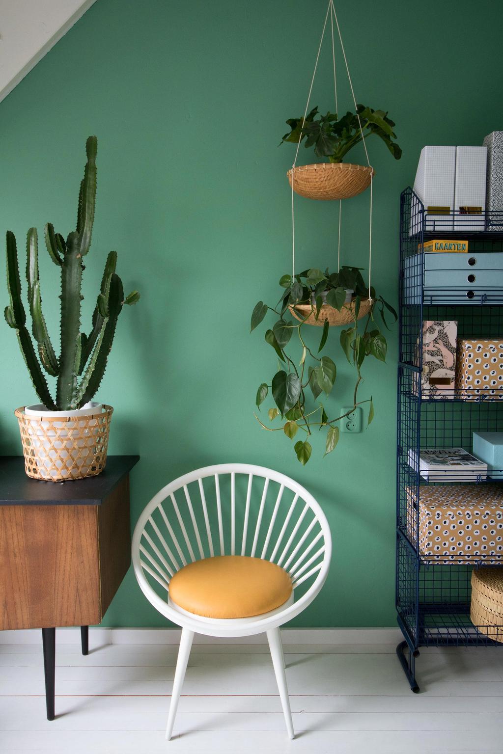 Plantenhanger voor een groene muur en met een stoel en kasten