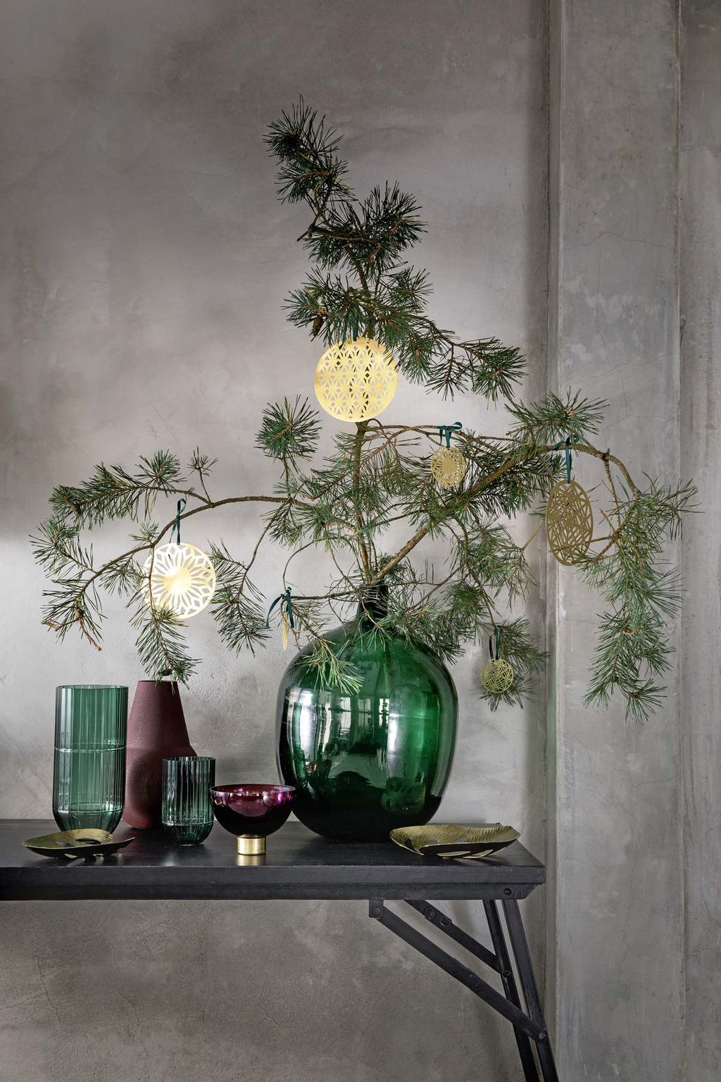 Een kersttak in een groene vaas met papier gouden kerstballen uit de feest special.