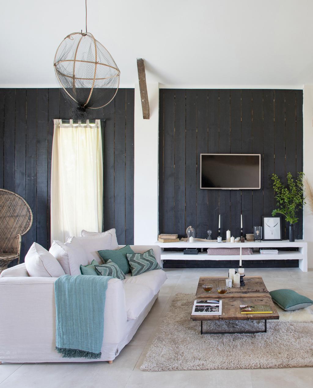 vtwonen 05-2021 | grijze bank met zwarte houten planken op de muur