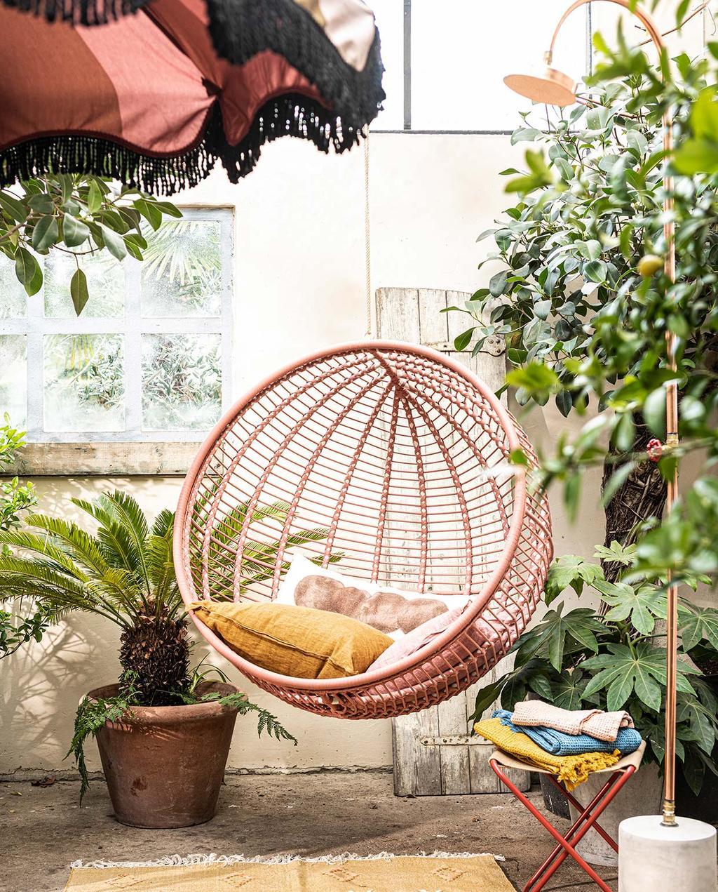 vtwonen 07-2021 | ronde roze hangstoel in de tuin met een okergeel kussen
