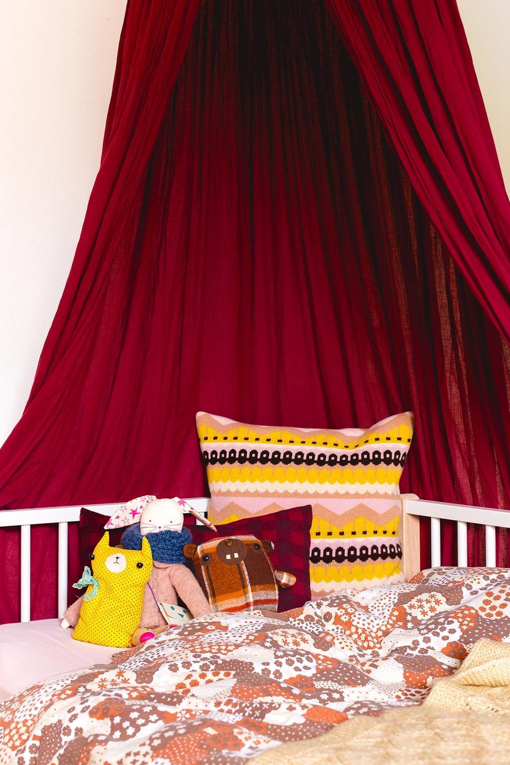 Rode klamboe boven een kinderbed met vintage dekbedovertrek