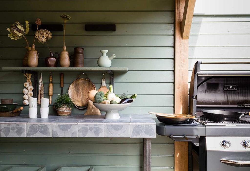 Buitenkeuken in een tuinhuis met betegeld aanrecht en barbeque
