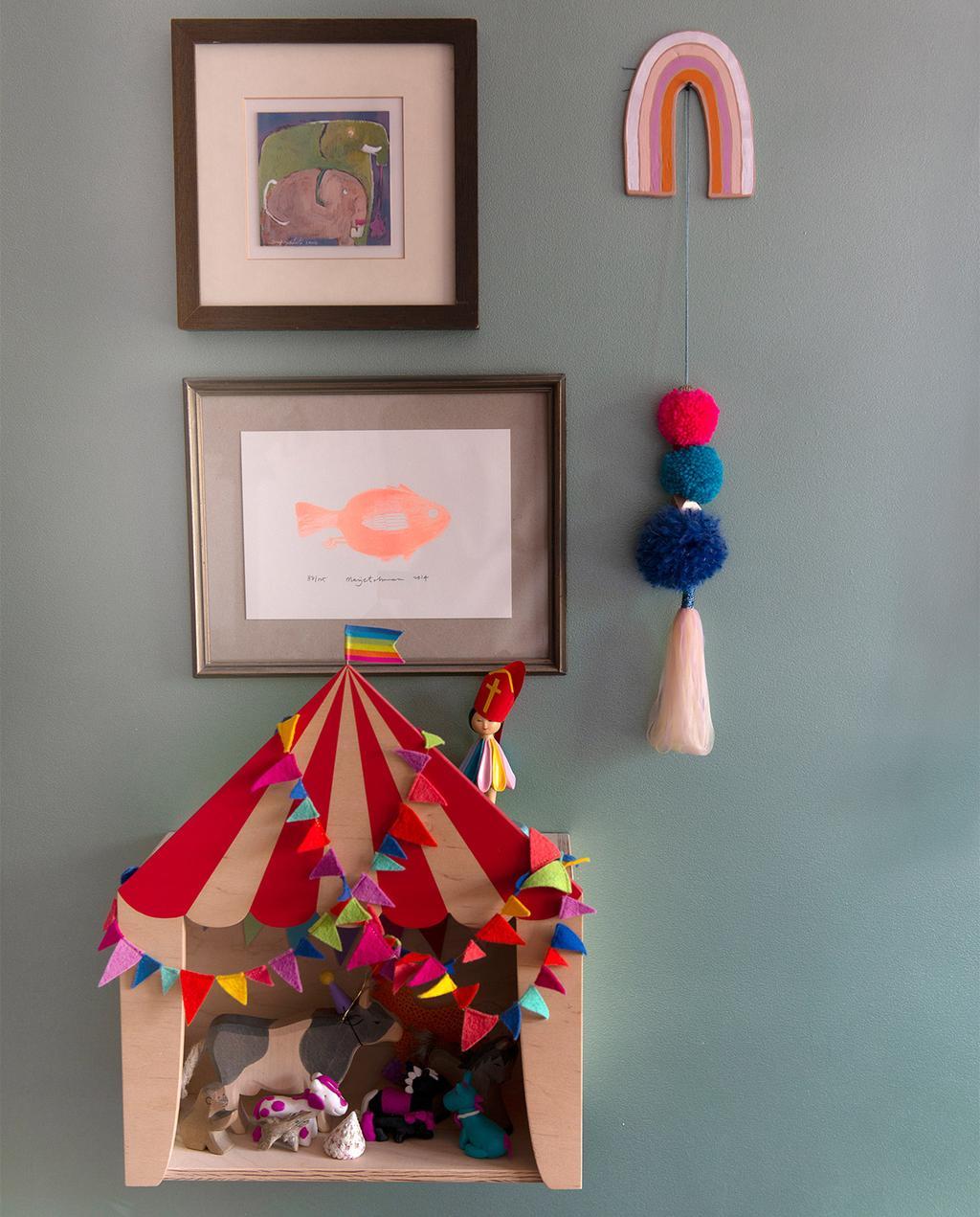vtwonen 07-2021   speelgoed huis hangend aan de muur met twee schilderijtjes en een regenboog hanger