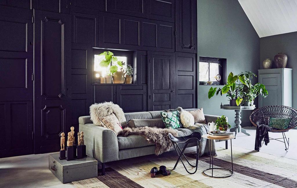 Warm interieur met een zwarte wandkast, grijze bank en warme materialen