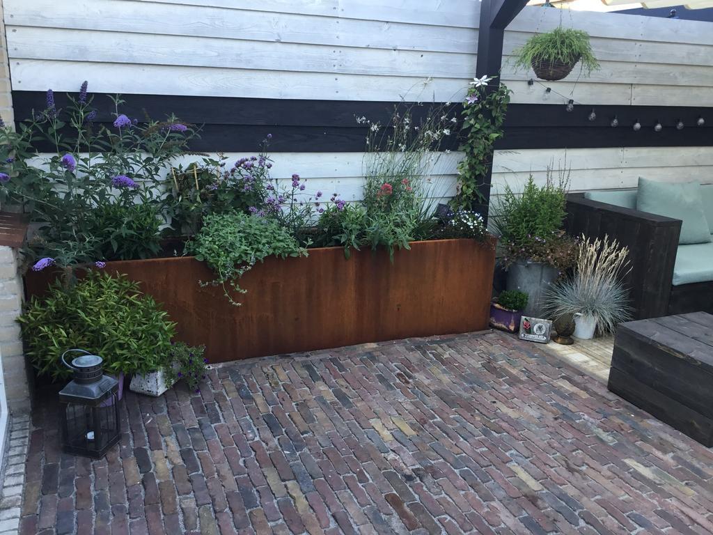 onze-tuin-is-klaar-super-blij-mee-wat-hebben-wij-allemaal-gedaan-nou-eigenlijk-alles-wat-in-de-tuin-staat-is-quot-aangeraakt-quot-de-gepotdekselde-schutting-is-nogmaals-gewit-en-er-zijn-2-zwarte-banen-opgezet-de-andere-schutting-is-zwart-geverfd-en-het-stuk-muur-daarnaast-mat-zwart-geverfd-grote-steigerhouten-loungeset-die-zwart-is-gebeitst-waar-wij-met-het-hele-gezin-lekker-op-kunnen-zitten-boven-deze-set-hebben-wij-een-zwarte-pergola-gezet-met-een-wittig-harmonicadoek-zit-je-echt-stik-gezellig-zo-ook-hebben-wij-2-grote-corten-stalen-bloembakken-op-maat-laten-maken-waar-wij-de-wildere-planten-in-hebben-gezet-de-bestrating-hebben-wij-vervolgens-gelegd-met-oude-gebakken-waaltjes