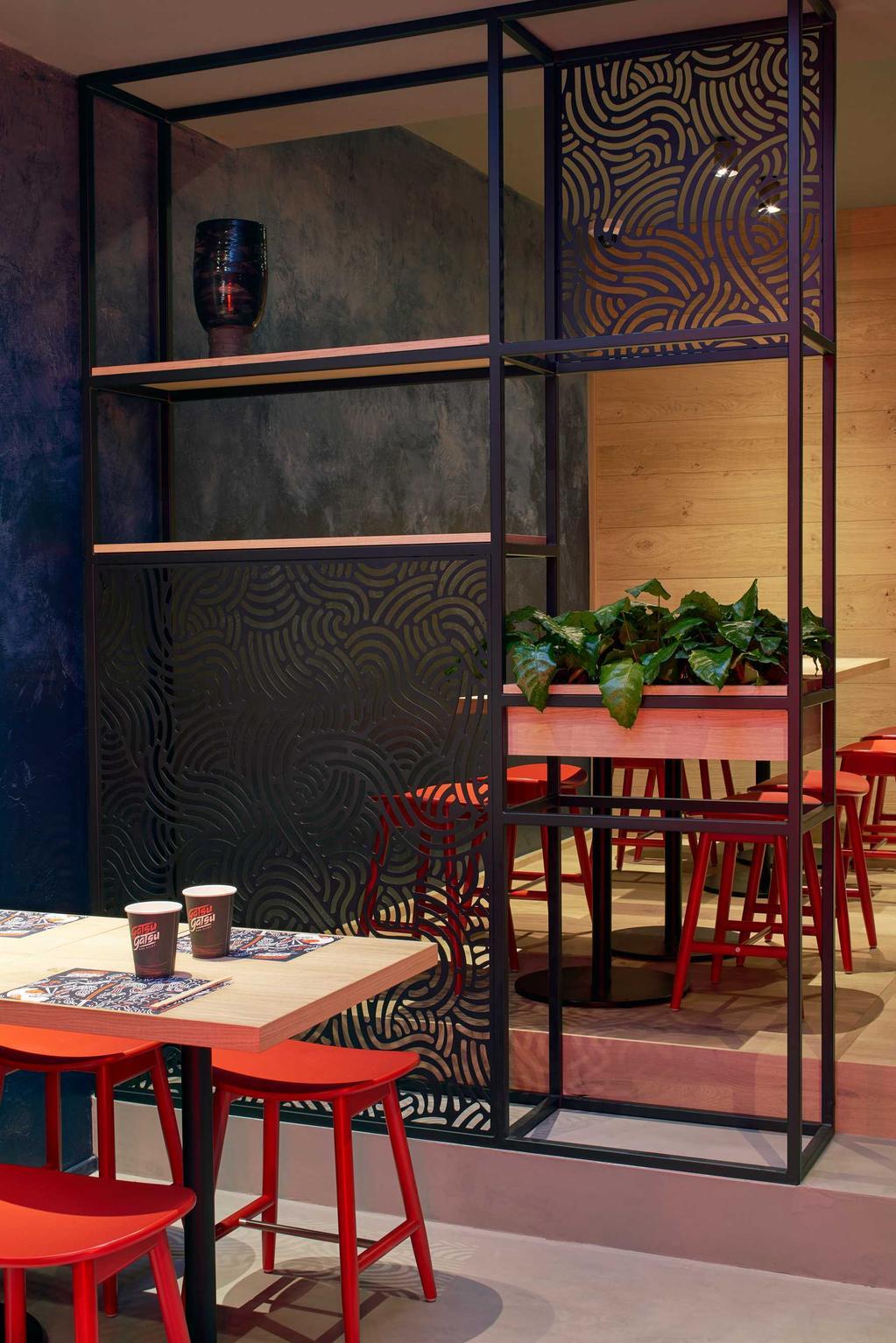 gatsugatsu interieur met groene muur en rode stoelen en plant