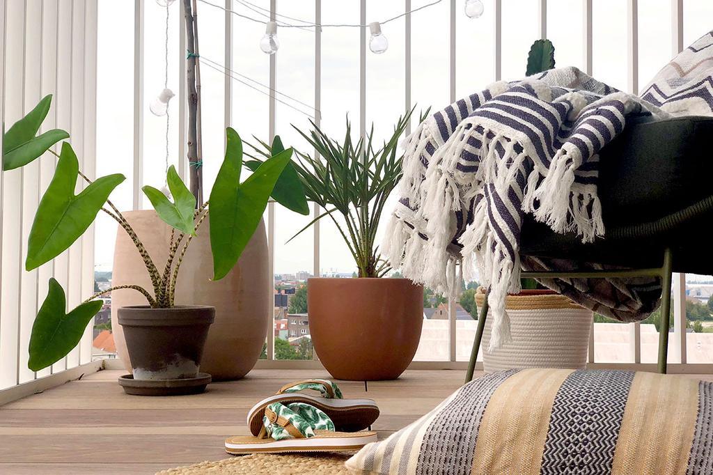 Een stoel met dekentje staat naast planten op een balkon.