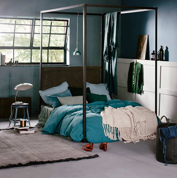 slaapkamer krukje met stalen bedframe en blauwe lakens
