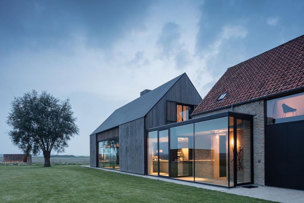 Een gebouw van hout en glas in het avondlicht.