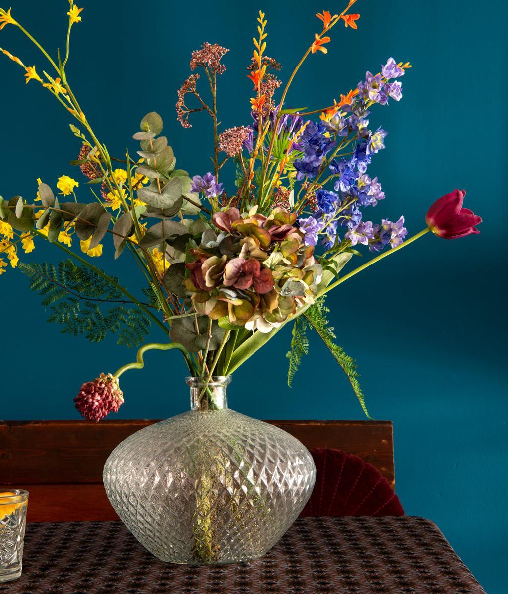 blauwe muur met daarvoor een transparante vaas met boeket bloemen  | indian summer