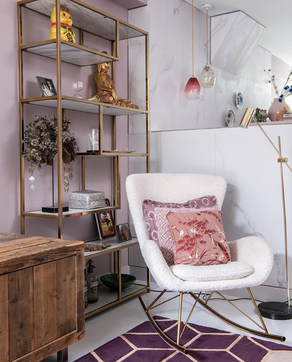 vtwonen 06-2021 | witte schommelstoel met gouden open kast en een houten dressoir