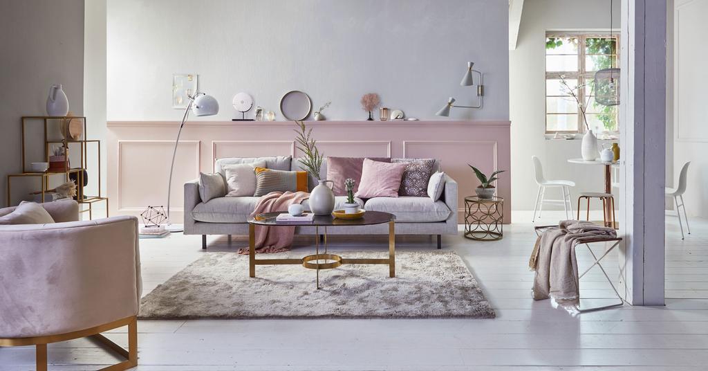 Een poederroze woonkamer met koperen details en roze lamberisering