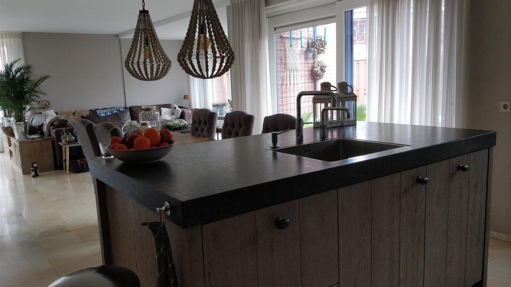 vanuit-de-keuken-zicht-op-de-woonkamer-en-ook-de-tuin