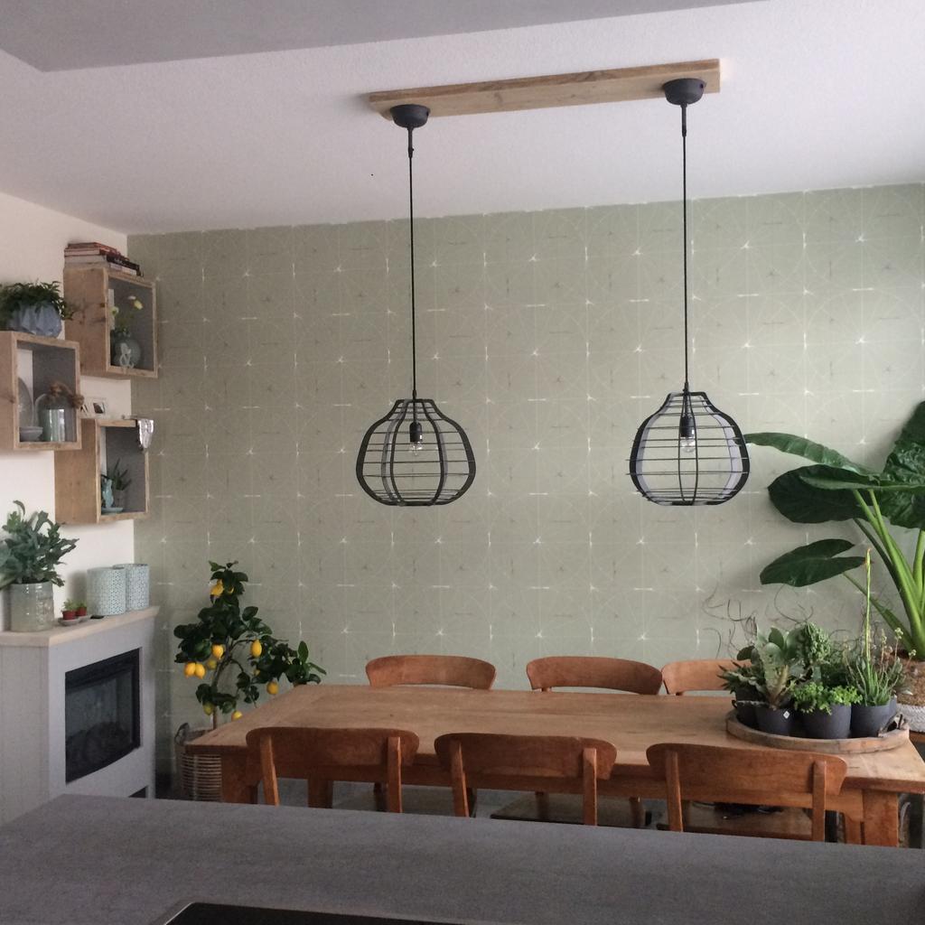 vanuit-de-open-keuken-met-kookschiereiland-kijken-we-naar-onze-eettafel-waar-door-onze-erker-veel-licht-naar-binnen-komt-omdat-we-door-de-vloerverwarming-nog-wat-warmte-miste-bij-de-eettafel-hebben-we-een-elektrische-haard-geplaatst-van-de-gamma-in-bijpassende-houten-schouw-om-deze-te-laten-aansluiten-bij-de-steigerhouten-kubussen-heb-ik-de-bovenkant-kaal-gemaakt-en-de-binnenzijde-van-de-kubussen-grijs-geverfd-het-behang-is-van-rebel-walls-45-per-m2-maar-wel-heel-mooi-en-kwalitatief-goed-de-lampen-van-hk-living-maak-het-een-stoer-geheel-de-snoeren-aan-het-plafond-weggewerkt-door-in-de-steigerhouten-plank-aan-de-bovenzijde-een-gleuf-te-frezen-veel-groen-maken-het-een-gezellige-woonkeuken