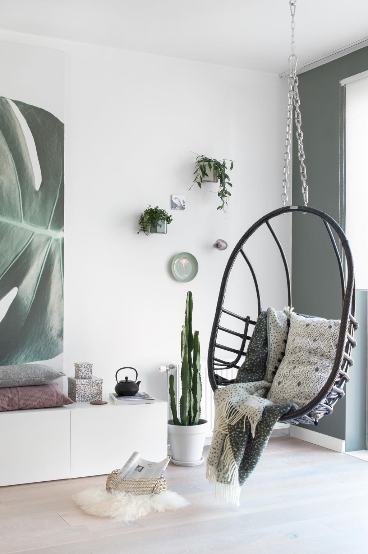 Hangstoel in een woonkamer met groene tinten in het voorjaarshuis van blogger Tanja