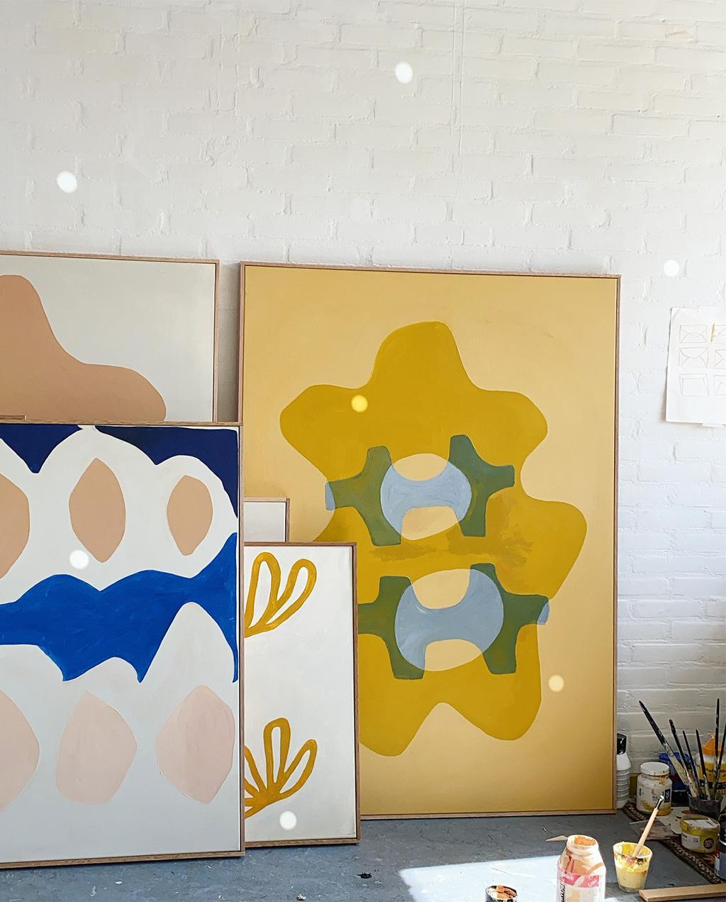 vtwonen 12-2020 | verschillende kunstwerken van kunst Anne Olde Kalter, links blauw met roze cirkels, rechts is een geel kunstwerk met groene details