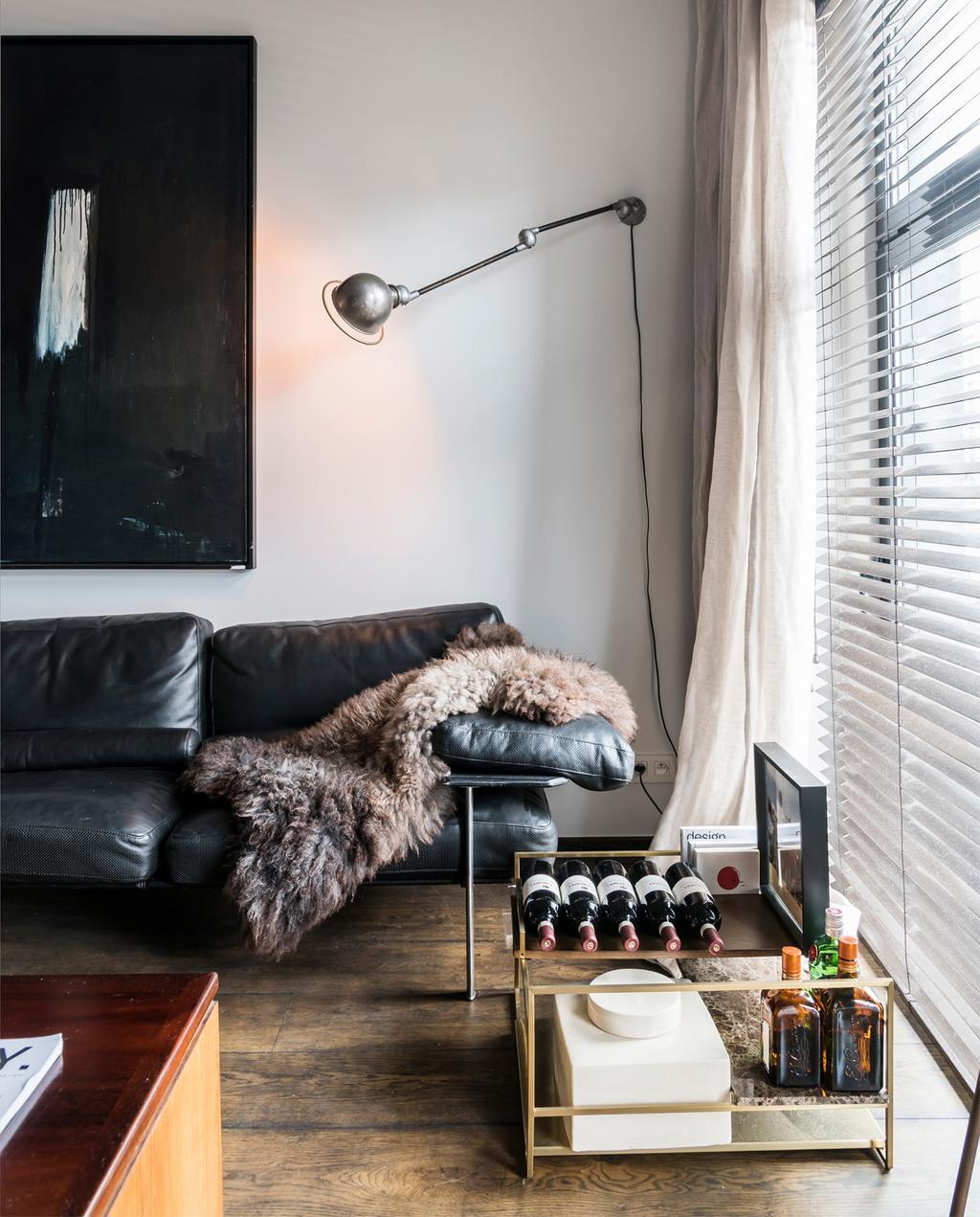 vtwonen 10-2020 | Appartement vol vintage design in Antwerpen vintage zwarte leren bank, wijnrek en zwart schilderij