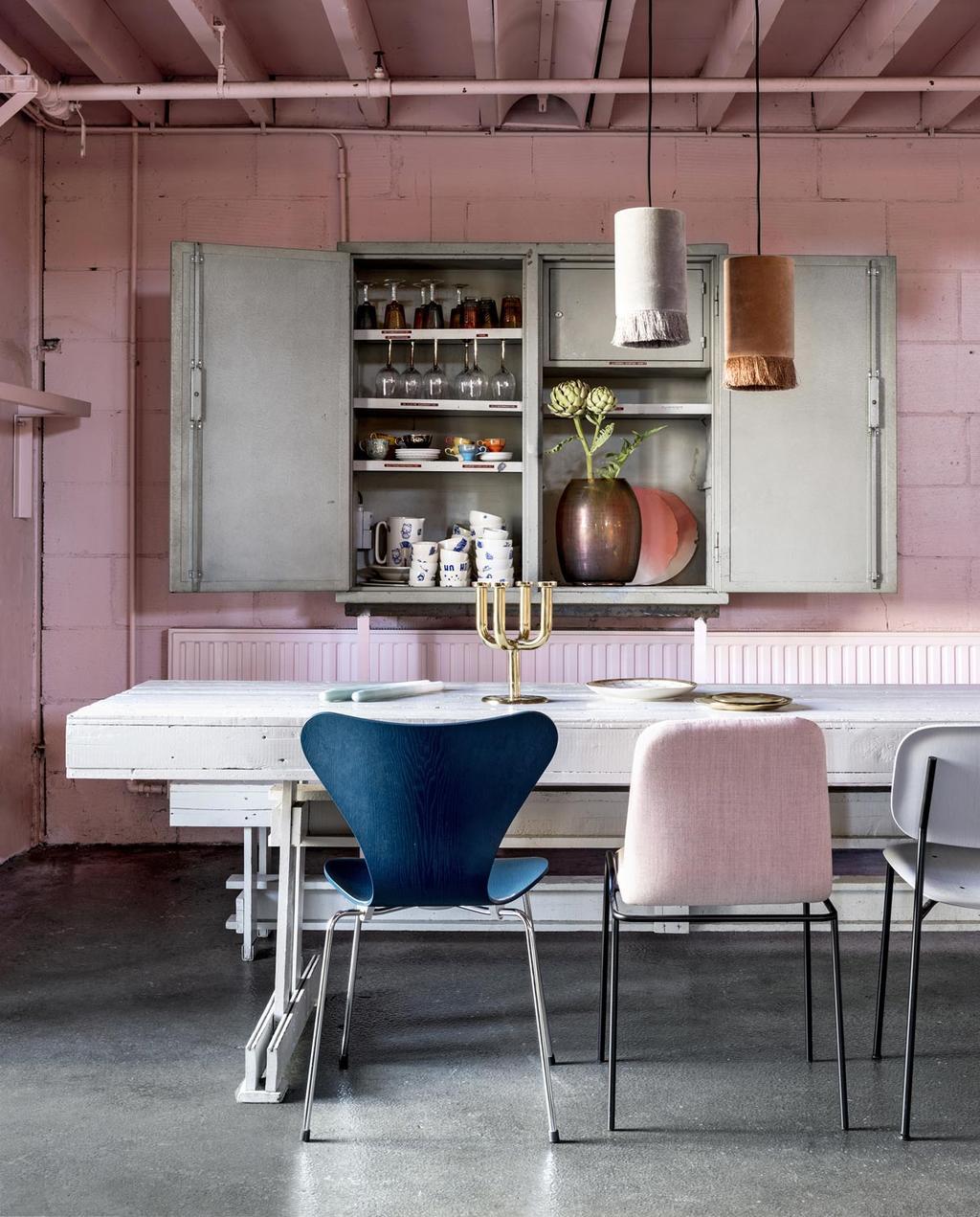 Een eetruimte met roze en blauwe accenten voor een warme gloed in huis.